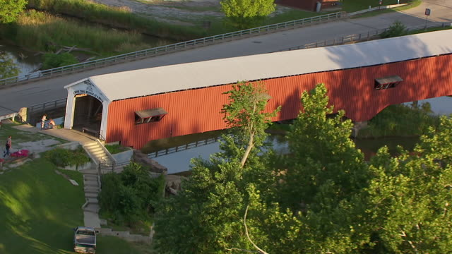 ws zo aerial pov thorpe ford covered bridge over river, buildings in background / parke county, rosedale, indiana, united states - wood material stock videos & royalty-free footage