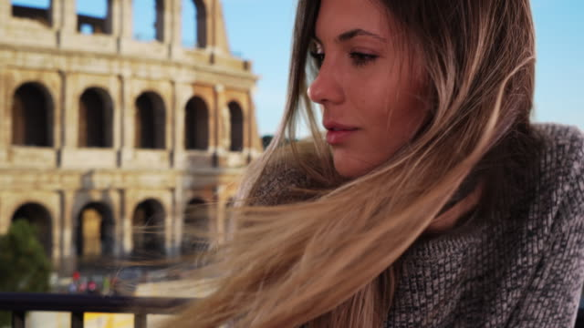 vídeos de stock, filmes e b-roll de thoughtful and serious young lady looking to the side by colosseum in rome - brown hair