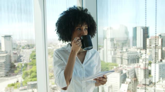 vidéos et rushes de femme d'affaires noire réfléchie de belle lecture quelque chose sur le bloc-notes tout en appréciant un café - mug