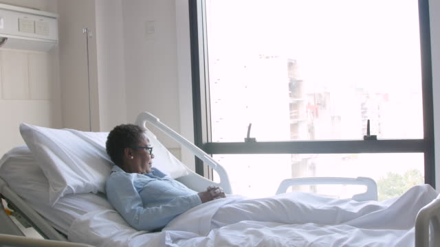 Thoughtful black female patient looking away to window while lying down on hospital bed