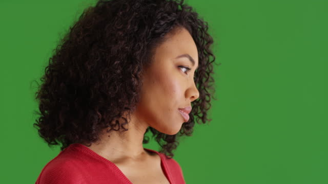 thoughtful black woman looking to the side turns toward camera on greenscreen - {{asset.href}} stock videos & royalty-free footage