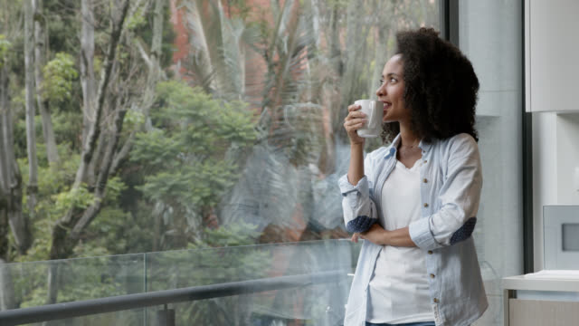 thoughtful black young woman enjoying a hot chocolate and looking at window view very relaxed - looking through window stock videos & royalty-free footage
