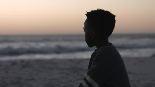 Thoughtful boy looking at sea during sunset