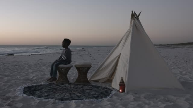 thoughtful boy sitting on stool by teepee at beach - serenità video stock e b–roll