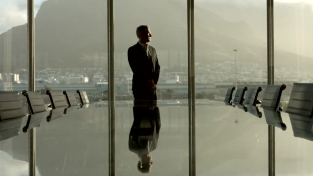 thoughtful businessman against window in office - anticipation stock-videos und b-roll-filmmaterial