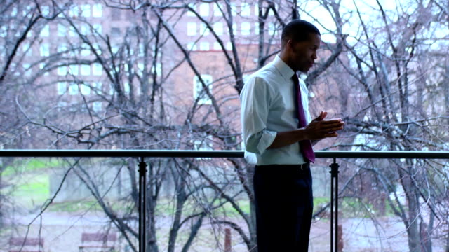 Thoughtful Businessman Looks out Window - WS