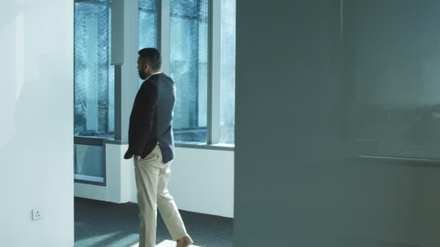 thoughtful businessman walking in office corridor - one man only stock-videos und b-roll-filmmaterial