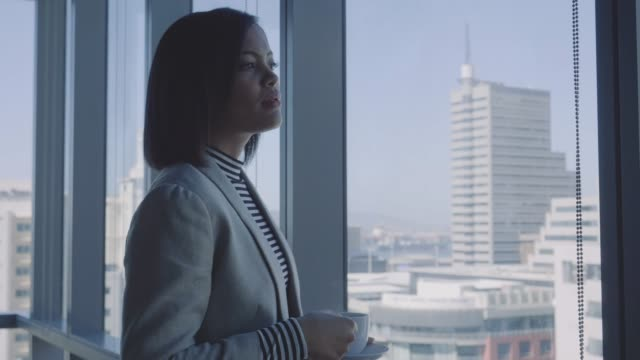 thoughtful businesswoman holding coffee cup - anticipation stock-videos und b-roll-filmmaterial