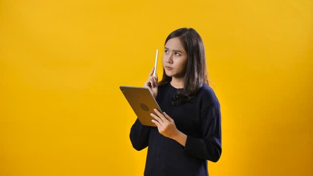 vidéos et rushes de fille confuse pensive dans le fond jaune - en désordre