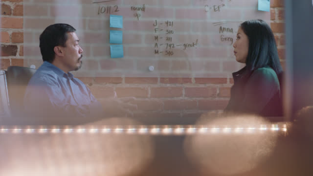 thoughtful coworkers have a one-on-one discussion in a small office - interview event stock videos & royalty-free footage