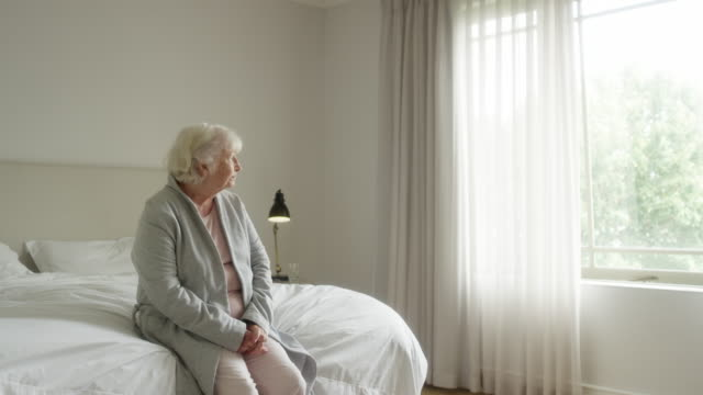 vídeos de stock e filmes b-roll de thoughtful elderly woman sitting on bed - sadness