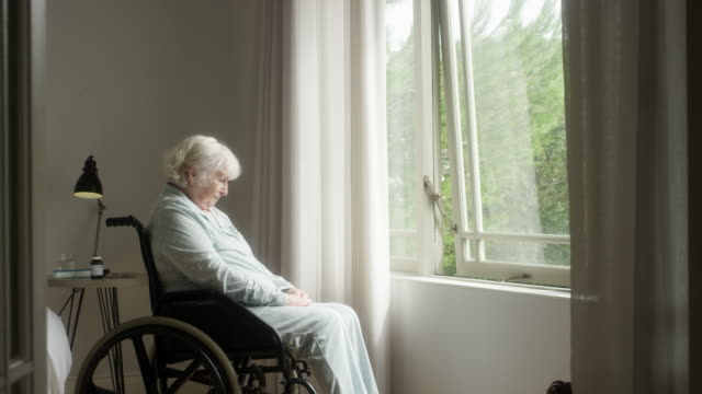 thoughtful elderly woman sitting on wheelchair - looking through window stock videos & royalty-free footage