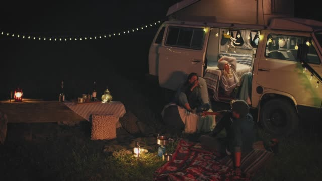 thoughtful friends relaxing while camping at night - van vehicle stock videos & royalty-free footage