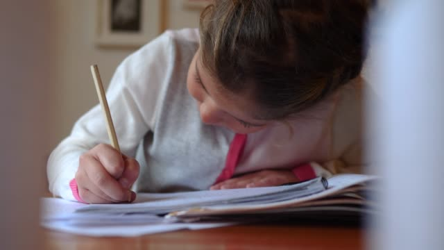 thoughtful girl doing math homework sitting in room at home - kind im grundschulalter stock-videos und b-roll-filmmaterial