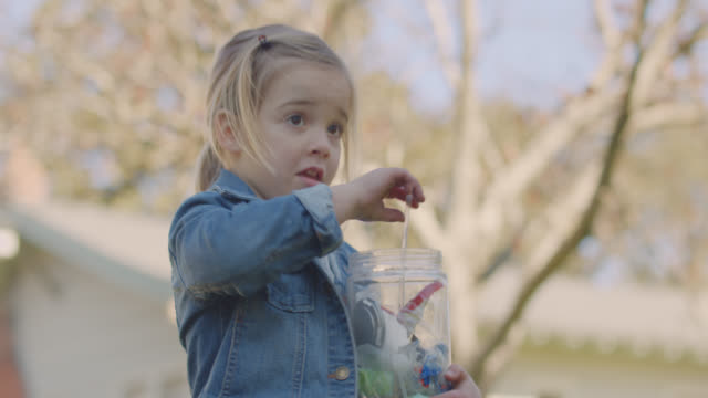 thoughtful girl picks up plastic straw from the ground outside, places it in jar of trash - collection stock videos & royalty-free footage