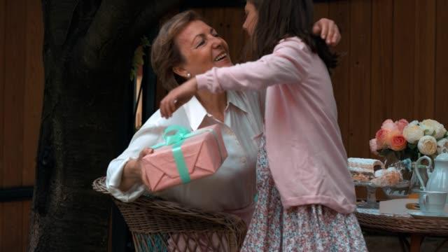 思いやりのある女の子の驚きの祖母 - 渡す点の映像素材/bロール