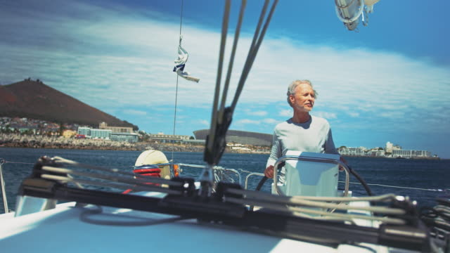 thoughtful man steering yacht in summer vacation - helm stock videos & royalty-free footage