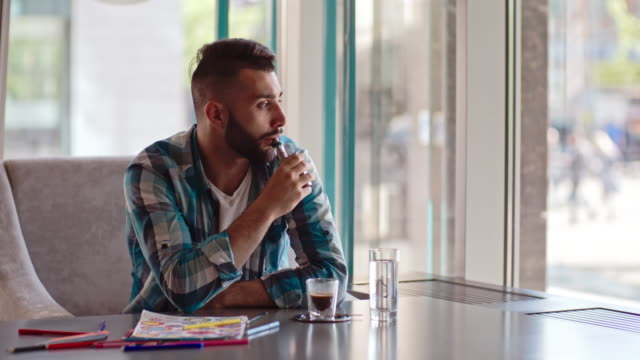 Thoughtful man vaping after coloring book
