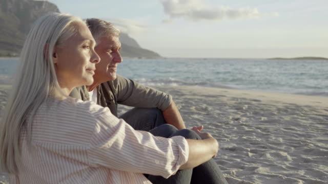 vídeos de stock e filmes b-roll de thoughtful mature couple sitting on sandy beach - casal de meia idade