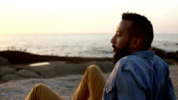 Thoughtful mixed-race man sitting on rock at beach during sunset 4k