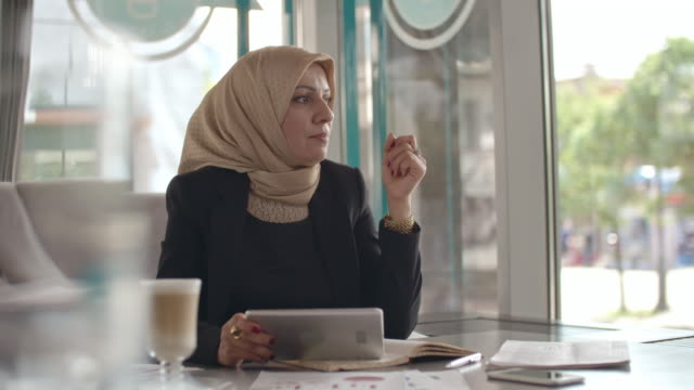Thoughtful Muslim businesswoman working from cafe