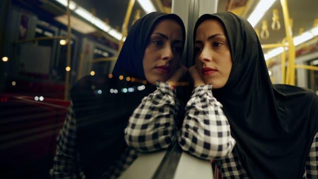 vídeos y material grabado en eventos de stock de mujer musulmana pensada en el tren - inmigrante