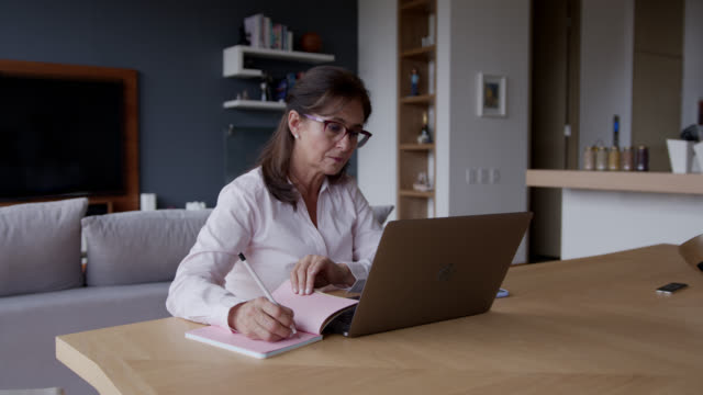 thoughtful senior woman working from home using notepad and laptop looking away - wellbeing stock videos & royalty-free footage