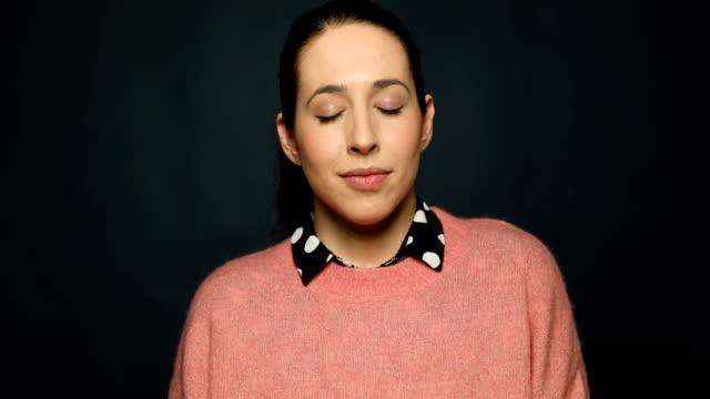 stockvideo's en b-roll-footage met doordachte lachende vrouw met gesloten ogen - formeel portret