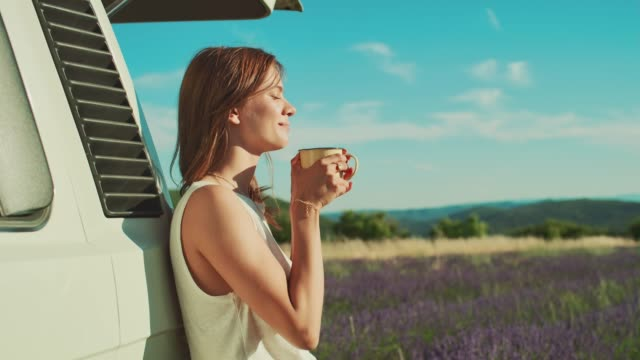 thoughtful woman against van enjoying coffee - telecamera traballante video stock e b–roll