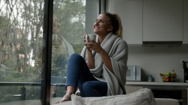 thoughtful woman at home on a cold day drinking tea and looking at the window - daydreaming stock videos & royalty-free footage