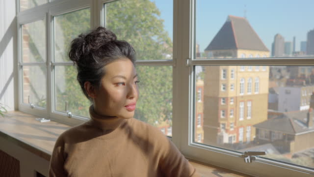 thoughtful woman looking out of office window - pacific islander stock videos & royalty-free footage