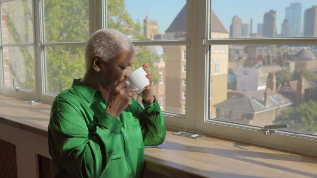 thoughtful woman looking out of office window while drinking from a cup - reflection stock videos & royalty-free footage