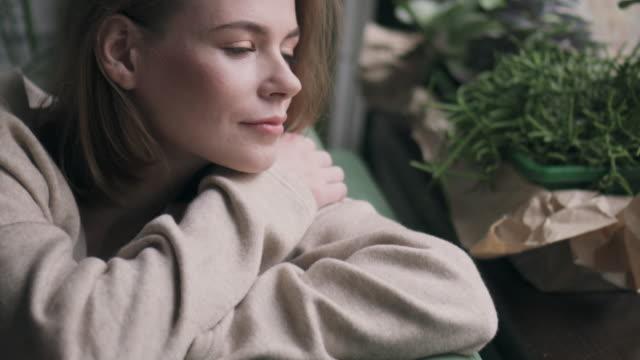 vidéos et rushes de réfléchie femme regardant par la fenêtre - pull