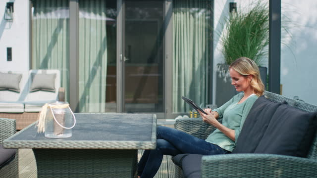 thoughtful woman using digital tablet at patio - patio stock videos & royalty-free footage