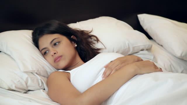 vídeos de stock, filmes e b-roll de pensativa mulher acordando e virando enquanto parceiro está dormindo mostrando suas costas - olhos fechados