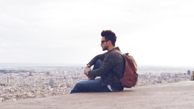 nachdenkliche junge männliche touristen sitzen in stadt - sonnenbrille stock-videos und b-roll-filmmaterial