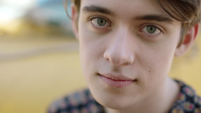 vídeos de stock e filmes b-roll de cu slo mo. thoughtful young man looks up and stares at camera. - sério
