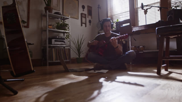 WS. Thoughtful young musician with acoustic guitar writes in notebook on apartment floor.