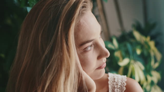 thoughtful young woman sitting in cafe - hand in hair stock videos & royalty-free footage