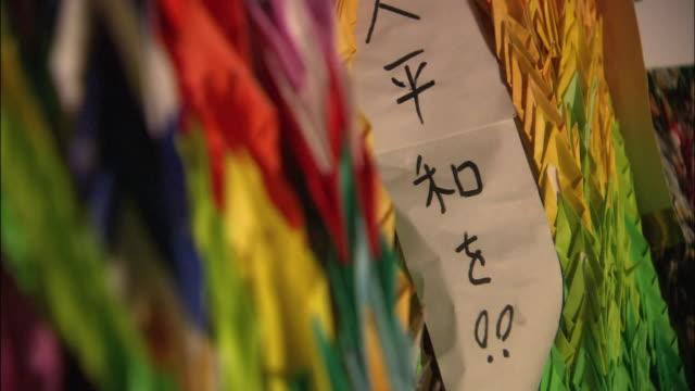 vídeos y material grabado en eventos de stock de thousand colorful origami cranes and the word wish for peace written on a paper strip zoom in - grulla de papel