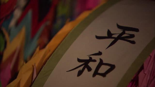 vídeos y material grabado en eventos de stock de thousand colorful origami cranes tilt down to the calligraphy heiwa written beautifully on a piece of paper - grulla de papel