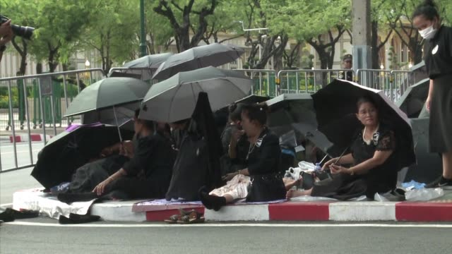 Thousands brave the heat and rain as officials begin letting Thais inside the crematorium ground ahead of the grand funeral of a late Thai king