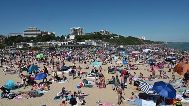 thousands crowd the beach in the english coastal town of bournemouth to soak up the sun on the hottest day of the year as lockdown measures are... - beach stock videos & royalty-free footage