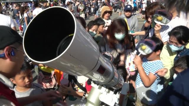 thousands flock to the taipei planetarium to watch the solar eclipse where a dozen telescopes have been set up to watch the phenomenon - dozen stock videos & royalty-free footage