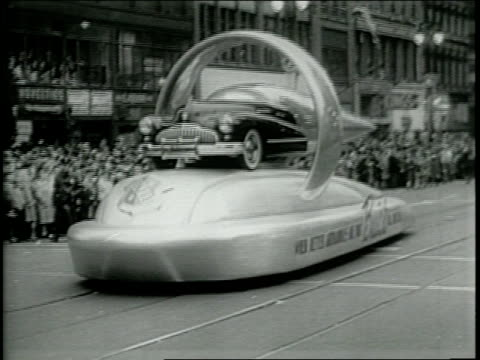 thousands gather along the sidewalks to watch a parade in downtown detroit celebrating 50 years of the automobile / a float carries a futuristic... - フォード・t型モデル点の映像素材/bロール