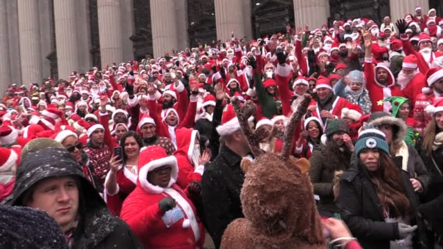 stockvideo's en b-roll-footage met thousands in santa claus suits gather for yearly santacon meets for their pub crawl at the farley square post office on 8th ave and 33rd street - postkantoor