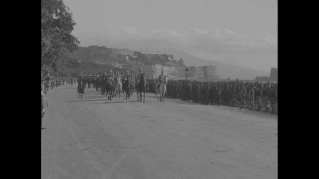 stockvideo's en b-roll-footage met thousands line long beach front road horse mounted troops led by prince umberto march toward camera pan across road where troops are massed along... - koninklijk persoon