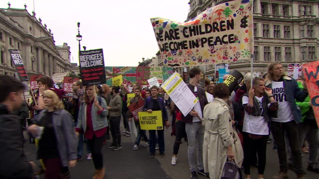thousands march in london during prorefugee demonstration - welcome segnale inglese video stock e b–roll