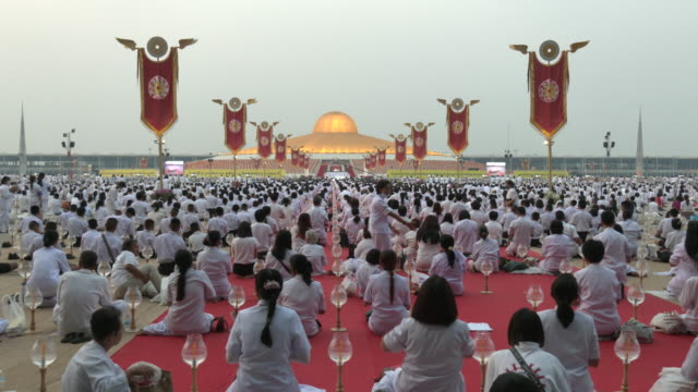 thousands of buddhist devotees and monks take part in evening prayers to mark makha bucha day at wat dhammakaya temple, just north of bangkok. makha... - praying stock videos & royalty-free footage