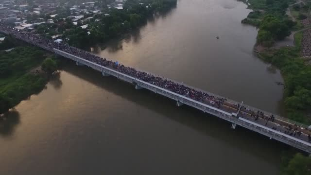 thousands of central american migrants wait on the guatemala mexico border bridge in hopes of continuing their journey toward the united states - refugee stock videos & royalty-free footage